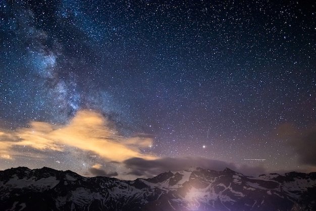 Milky way starry sky rocky mountains at high altitude on the alps. Premium Photo