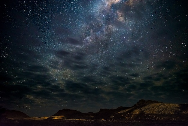 Milky way stars in the sky, the namib desert in namibia, africa. some scenic clouds. Premium Photo