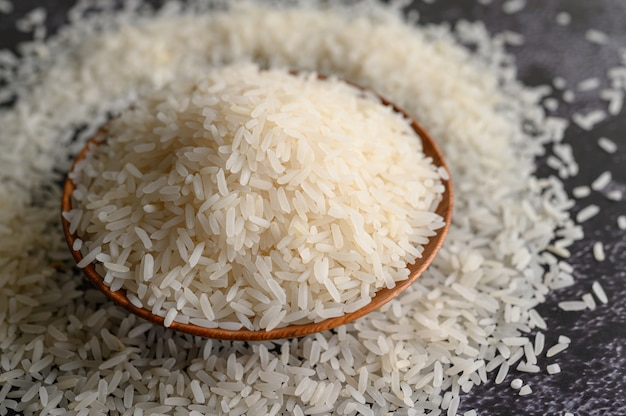 Milled rice in a bowl and a wooden spoon on the black cement floor. Free Photo