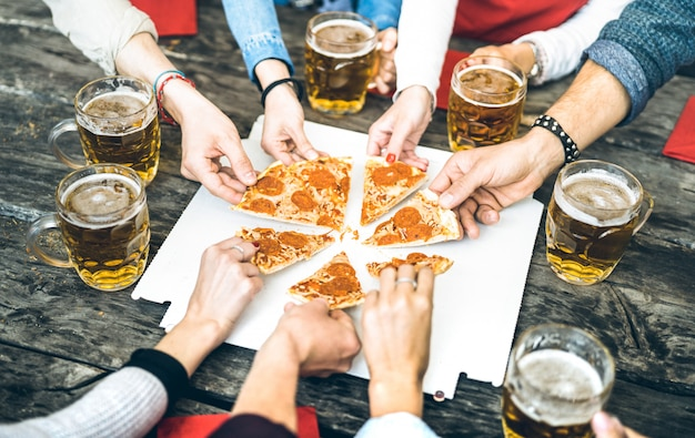Millenial friends group drinking beer and sharing pizza slices at bar restaurant Premium Photo