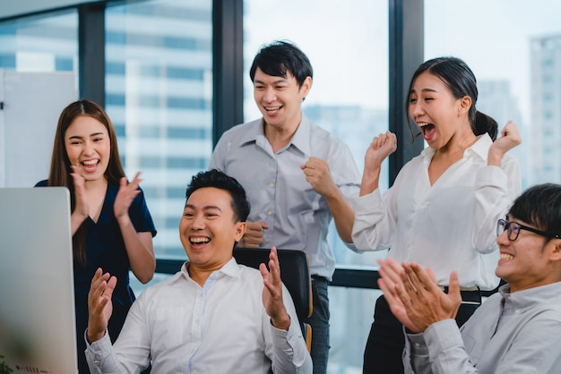 Millennial group of young businesspeople asia businessman and businesswoman celebrate giving five after dealing feeling happy and signing contract or agreement at meeting room in small modern office. Free Photo