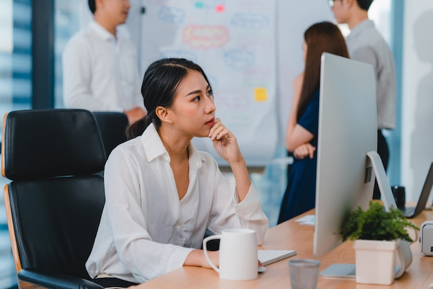 Millennial young chinese businesswoman working stress out with project research problem on computer desktop in meeting room at small modern office. asia people occupational burnout syndrome concept. Free Photo