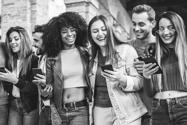 Друзья миллениалов гуляют вместе за пределами университета. молодые студенты веселятся с помощью смартфонов. молодежь, образ жизни, дружба и взаимопонимание. сосредоточьтесь на двух центральных лицах девушек Premium Фотографии