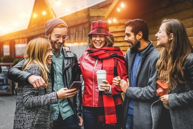 Счастливые молодые люди веселятся вместе из старинной пекарни - друзья millennials смеются, пьют кофе и используют смартфон - концепция путешествий и отдыха - сосредоточьтесь на лице девушки в центре Premium Фотографии