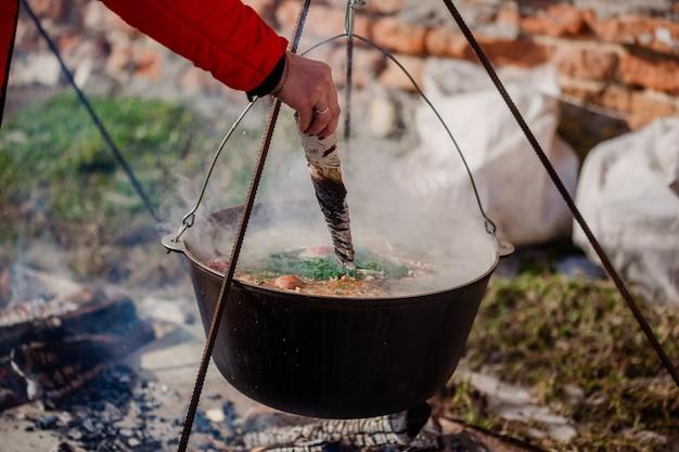 Пшенная каша с мясом, картофелем, луком, чесноком, зеленью, солью и специями. готовим украинское национальное блюдо в металлической посуде на открытом огне Premium Фотографии