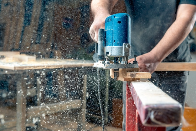 Milling wood in the joinery using manual mechanical cutters. flying sawdust in the air. copy space Premium Photo