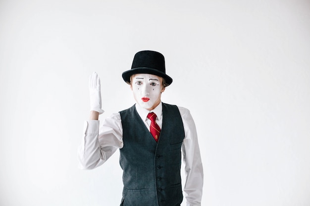 Mime in black hat holds his hand up like a pupil Free Photo