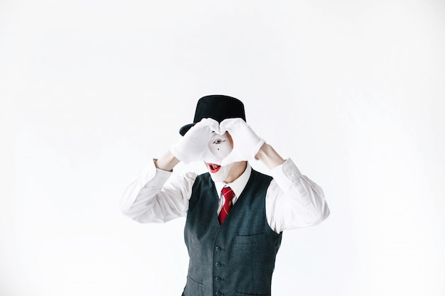 Mime in black hat looks through his fingers making a heart Premium Photo