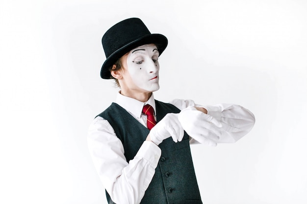 Mime in black hat and waistcoat looks at the invisible watch Free Photo