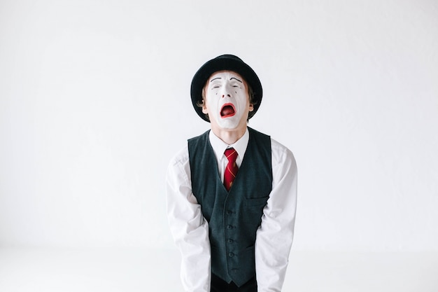 Mime in black hat and waistcoat screams on white background Free Photo