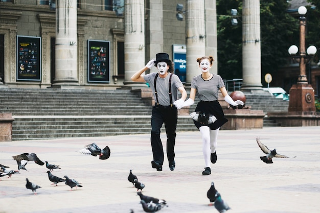 Mime couple holding hands running in front of building Free Photo