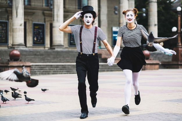 Mime couple running on city pavement Free Photo