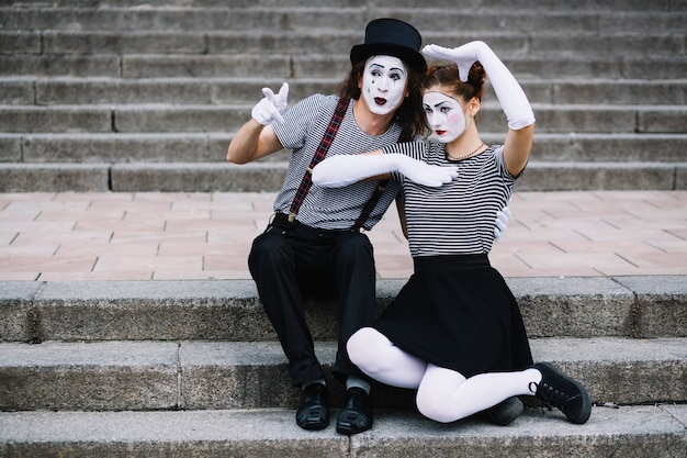 Mime couple sitting on staircase making gestures Free Photo