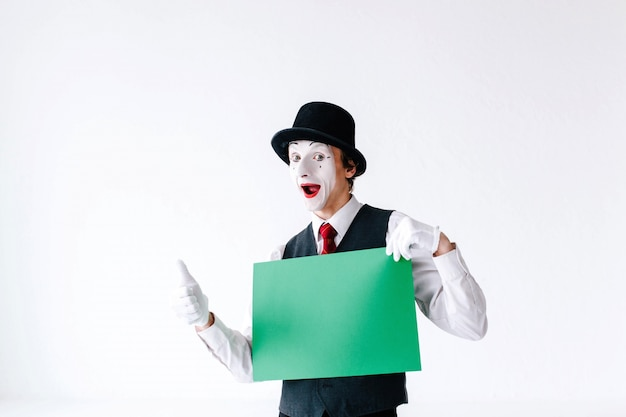 Mime holds thumb up before a green card Premium Photo
