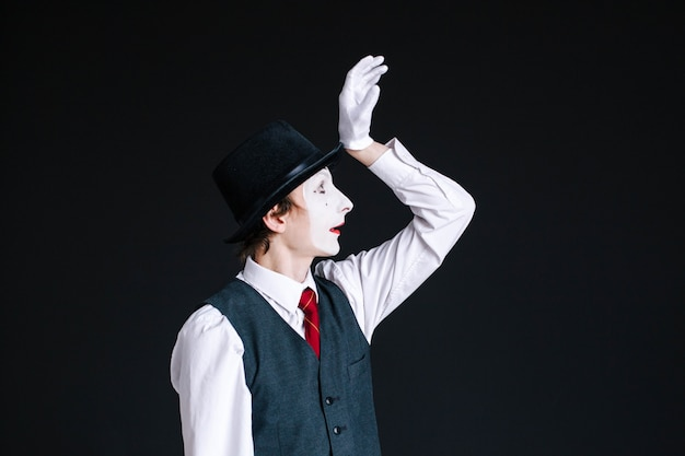 Mime raises his hand up posing on black background Free Photo