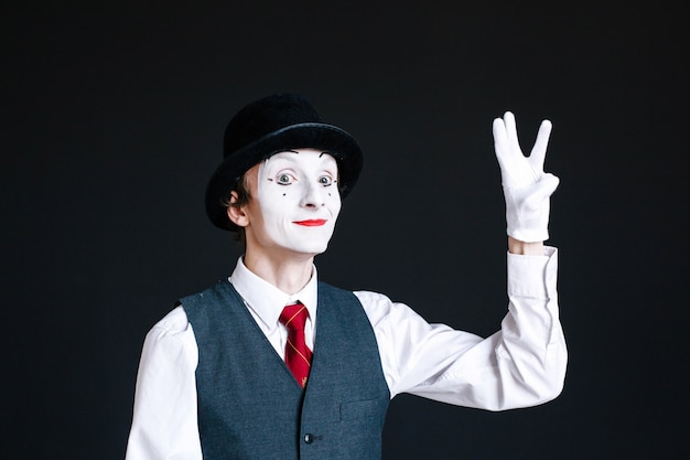 Mime shows sign of victory with his fingers Free Photo