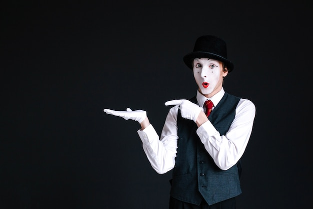 Mime shows at something invisible on his palm Free Photo
