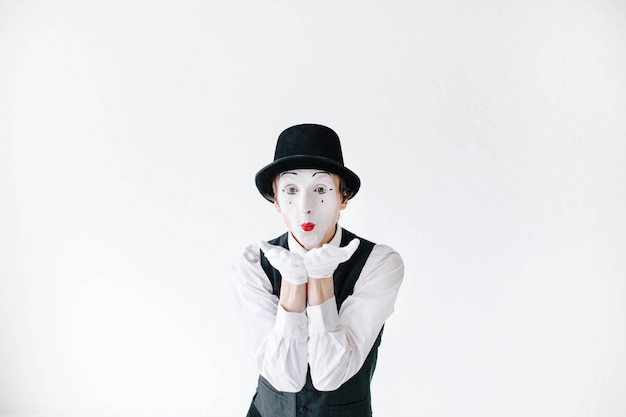 Mime with red lips sends an air kiss Free Photo