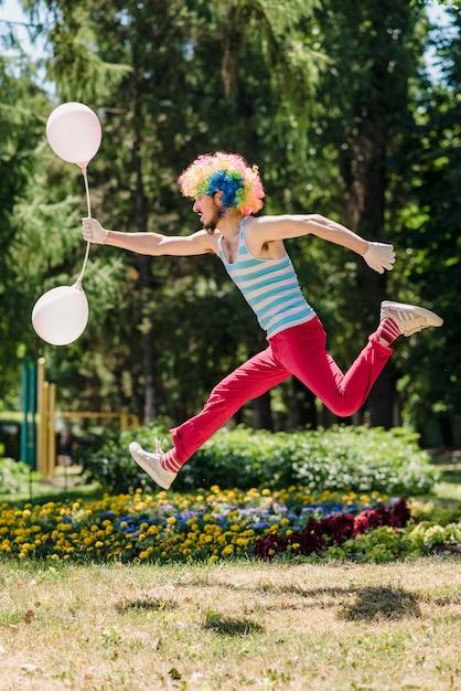 Mimeは風船で公園でジャンプします。 Premium写真