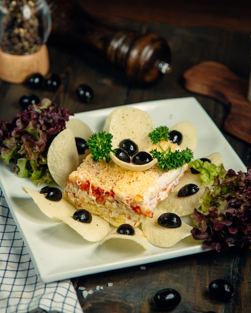 Mimosa salad ornated with chips and olives Free Photo