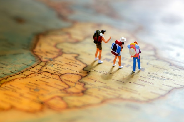 Minature people: traveling with a backpack standing on world map. Premium Photo
