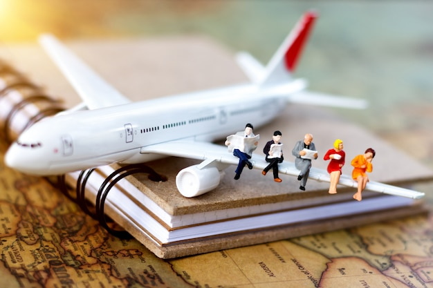 Minature people: traveling with reading book on plane. Premium Photo