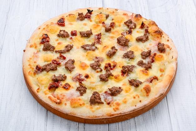 Фарш мясной томатный красный лук пицца на деревянной поверхности тонизирующий Premium Фотографии