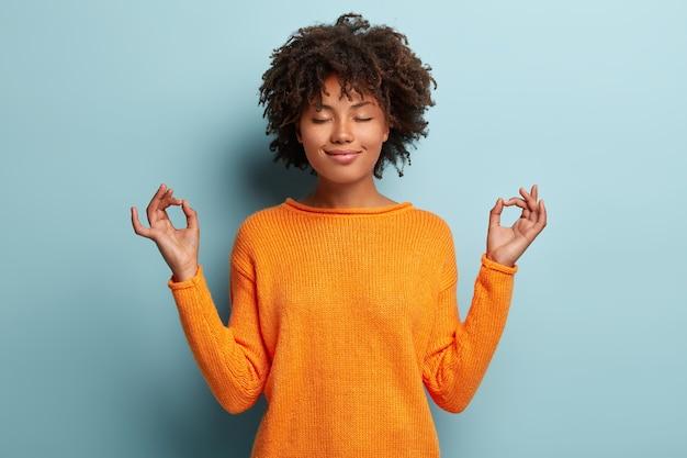마음 챙김 평화로운 아프리카 계 미국인 여성은 실내 명상, Mudra 제스처에 손을 유지, 눈을 감았습니다. 무료 사진