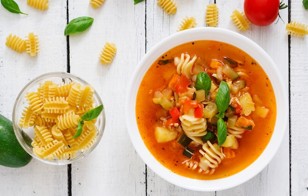 Minestrone, italian vegetable soup with pasta on white wooden table. top view Premium Photo