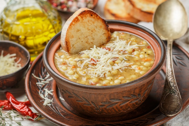 Minestrone, thick soup with vegetables , pasta, lentils, cheese and spices Premium Photo
