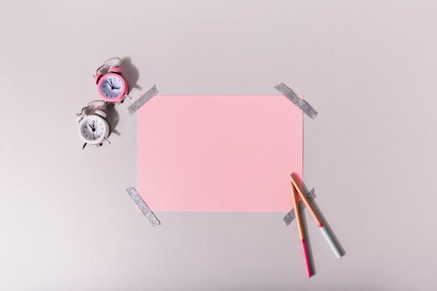 분홍색 편지지 세트 옆에있는 미니 알람 시계 무료 사진