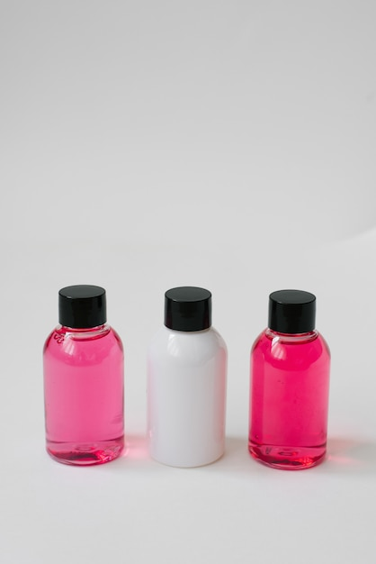 Mini bottles of pink and white color with body care cosmetics or hair on white background Premium Photo