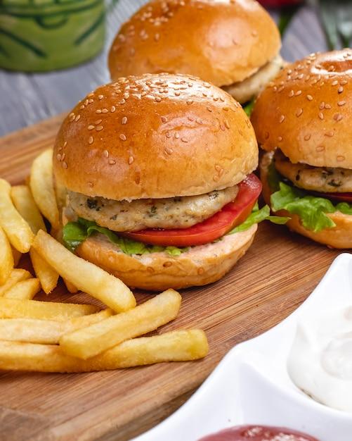 Vista laterale delle mini patate fritte della lattuga del pomodoro del pollo degli hamburger Foto Gratuite