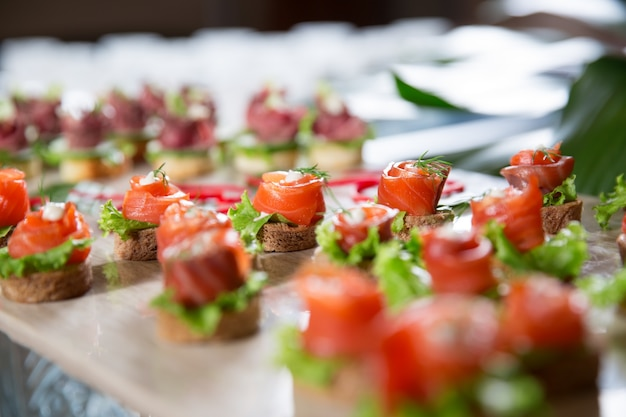 Mini canapes with smoked salmon on buffet table Free Photo