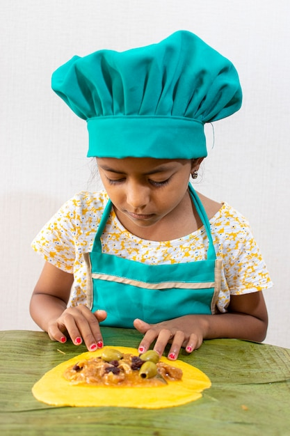Mini chef preparing typical venezuelan hallacas Premium Photo
