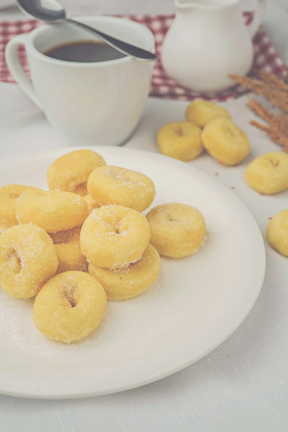 Mini donuts on white plate and a cup of coffee. Premium Photo