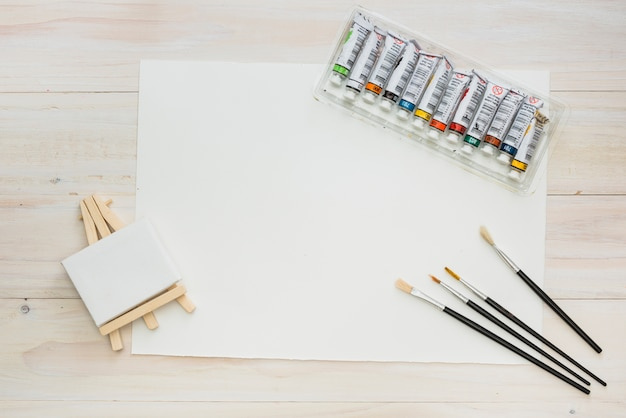 Mini easel with blank paper; brushes and paint tube on backdrop Free Photo