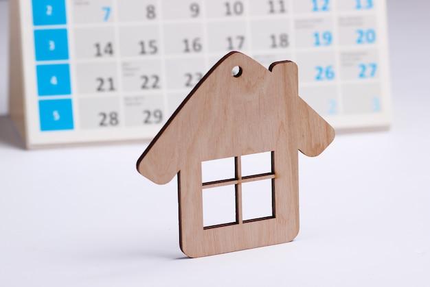 白い背景の上のデスクトップカレンダーとミニフィギュアの家。家賃支払いのコンセプト Premium写真