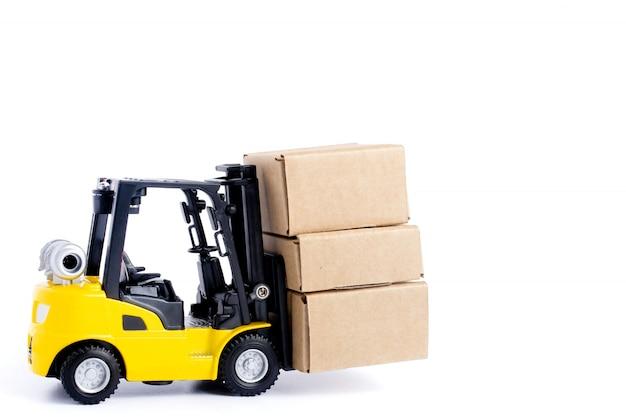 Картонные коробки нагрузки мини-погрузчика изолированные на белой предпосылке. идеи управления логистикой и транспортировкой и коммерческая концепция промышленного бизнеса. Premium Фотографии