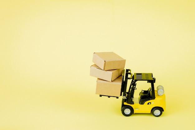 ミニフォークリフトトラックは、段ボール箱をロードします。ロジスティクスと輸送管理のアイデアと業界のビジネス商業コンセプト。 Premium写真