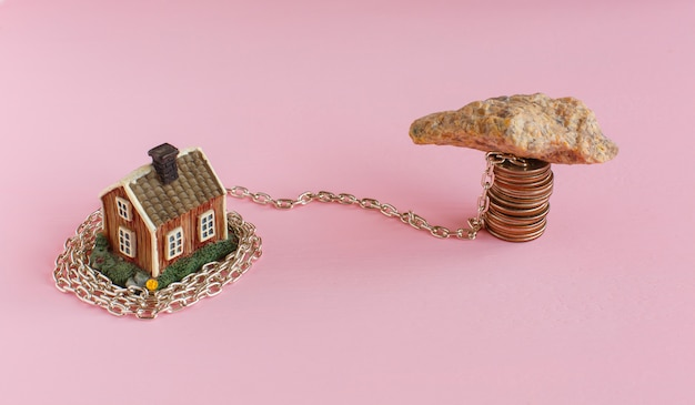 Mini house on pink is shrouded in chain and a heavy stone lies on the chain and near keys to the house. Premium Photo