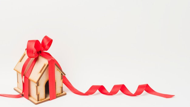 Mini house tied with red ribbon against white backdrop Premium Photo
