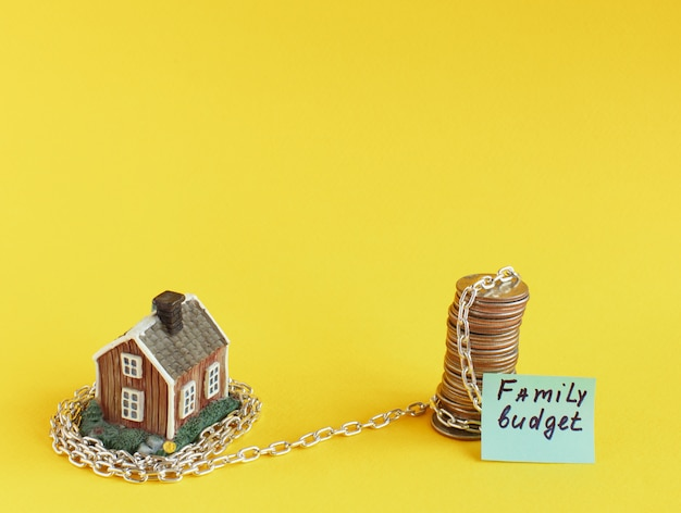 Mini house yellow is shrouded in chain. Premium Photo