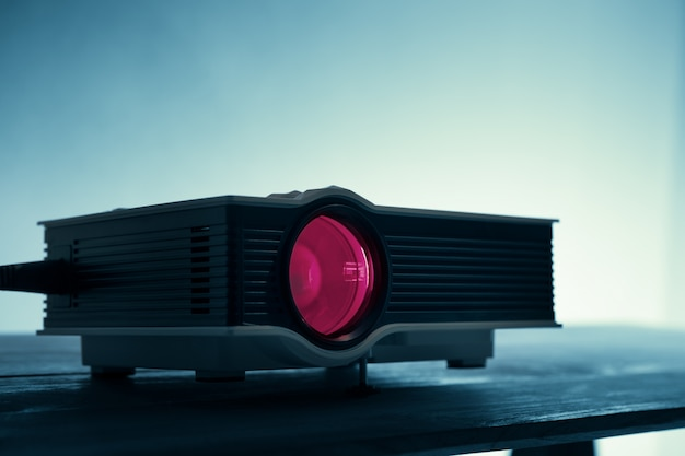 Mini led projector on table in dark blude tone projector home theater background. Premium Photo
