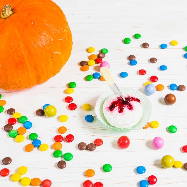 Mini muffin between little candies near pumpkin Free Photo