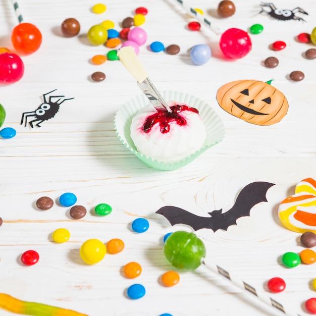 Mini muffin near little candies, bats, spiders and bonbon Free Photo