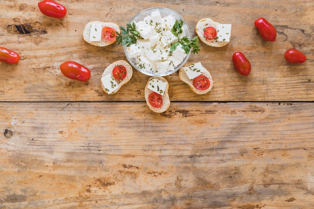 Mini sandwiches with cheese and tomatoes on wooden desk Free Photo
