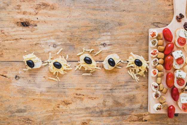 Mini sandwiches with grated cheese and black olives on wooden desk Free Photo