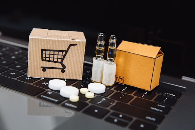 Mini shopping cart full of homeopathic remedies on laptop background. homeopathy and internet online shopping concept. Premium Photo