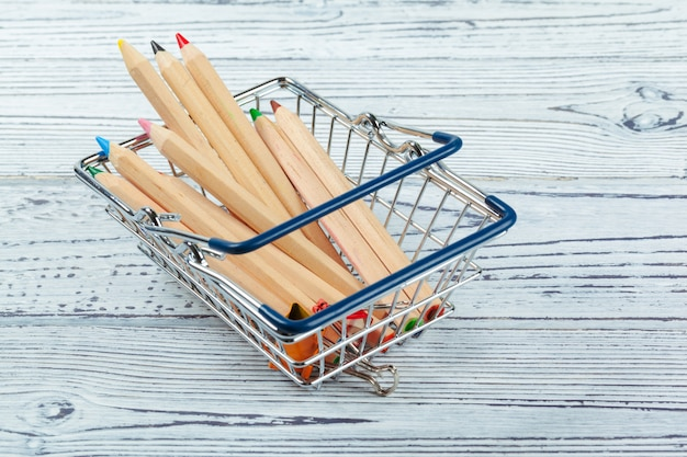 Mini shopping cart with multi-colored pens and pencils Premium Photo